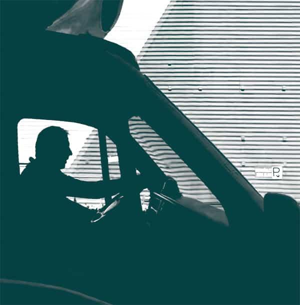 homme assis dans un camion qu'il conduit